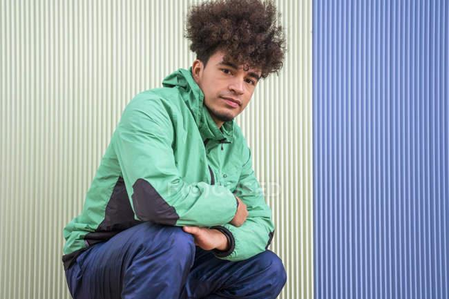 Uomo con acconciatura afro in abbigliamento attivo seduto su hunkers guardando la fotocamera con parete colorata sullo sfondo — Foto stock