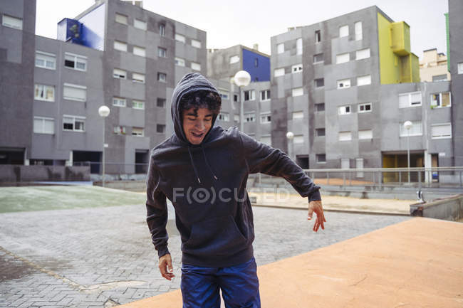 Man in hoodie standing with eyes down with city buildings on background at cold day — Stock Photo