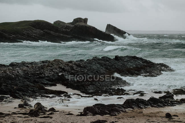 Scenery of small island near coast of Scotland on stormy daytime with misty hills and cliffs — Stock Photo