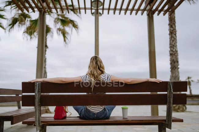 De derrière la vue de la femme avec à emporter tasse de café assis sur le banc de la ville en bord de mer le jour de l'été — Photo de stock