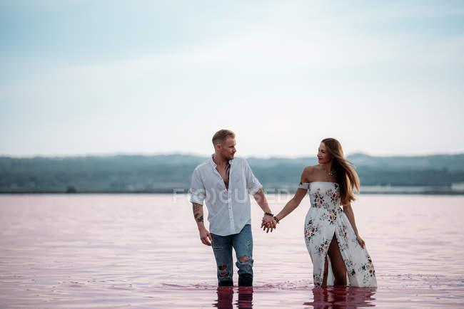 Adorable pareja caminando en un increíble lago rosa de agua de mar y cielo azul de la mano - foto de stock