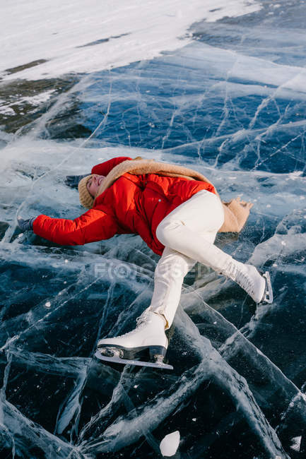 From above of happy young active female in warm active wear and skates lying on ice on frozen river and enjoying nice winter day in Siberia — Stock Photo