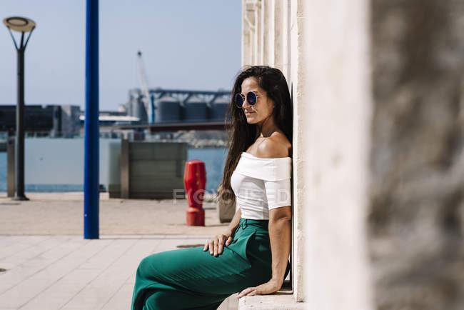Vue latérale d'une jeune belle femme hispanique avec des lunettes de soleil assises sur un banc de pierre contre un mur regardant loin — Photo de stock