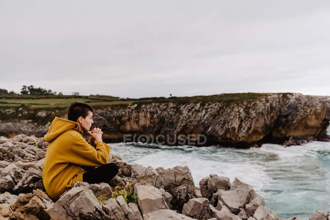 Vista lateral da mulher viajante com capuz quente amarelo sentado sozinho na costa rochosa olhando para ondas espumosas no dia nublado — Fotografia de Stock