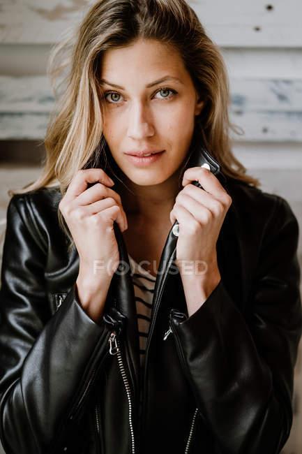 Elegante bella donna sicura di sé in giacca di pelle guardando la fotocamera sulla parete di legno — Foto stock