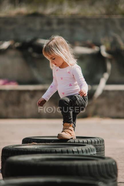 Felice gioiosa bambina divertirsi e camminare attraverso la fila di pneumatici auto nere mentre si gioca all'aperto il giorno d'estate — Foto stock
