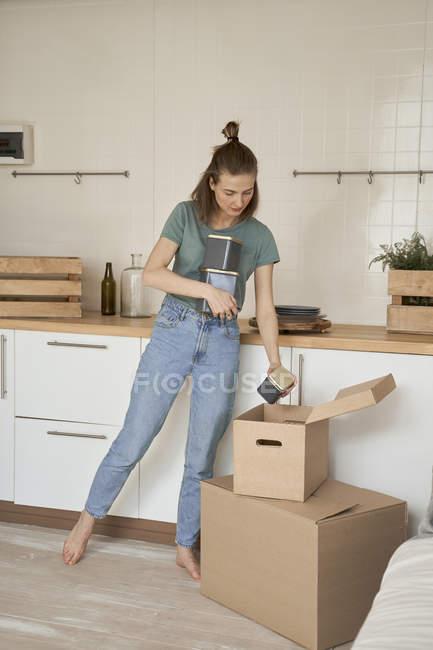 Mujer descalzo con vestimenta casual que tiene contenedores metálicos fuera de cajas de cartón en la cocina. - foto de stock
