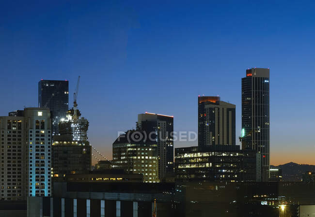 Drone view of illuminated metropolitan city with skyscrapers against cloudless dark blue sky at night — Stock Photo
