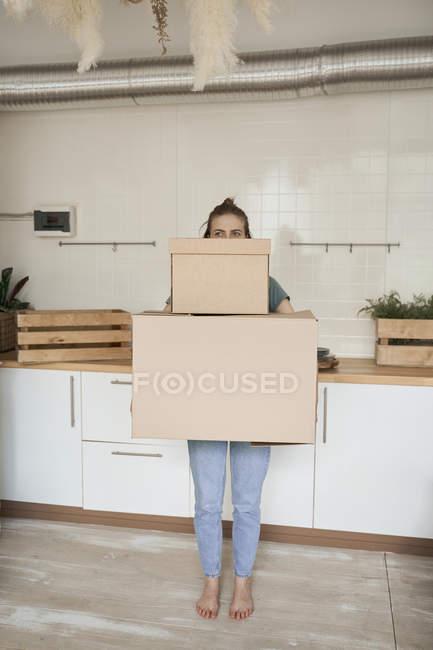 Mujer joven que se esfuerza y lleva cajas de cartón con cosas en casa. - foto de stock