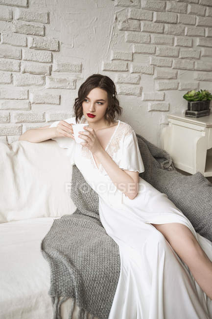 Pensive adult woman looking away and dreaming while sitting on sofa and having hot drink in light modern living room — Stock Photo