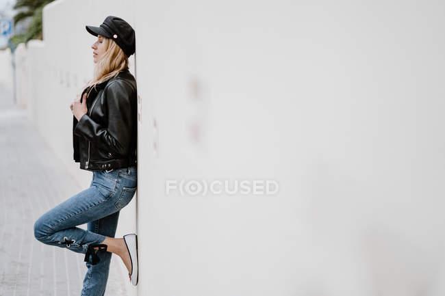 Бічний вид довговолосих блондинок у чорній шапці і куртка спираючись на стіну з піднятою ногою — стокове фото