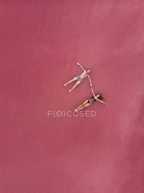 Aerial view of man and woman in swimsuits holding hands while floating on pink salty water of lake at Torrevieja at Spain — Stock Photo