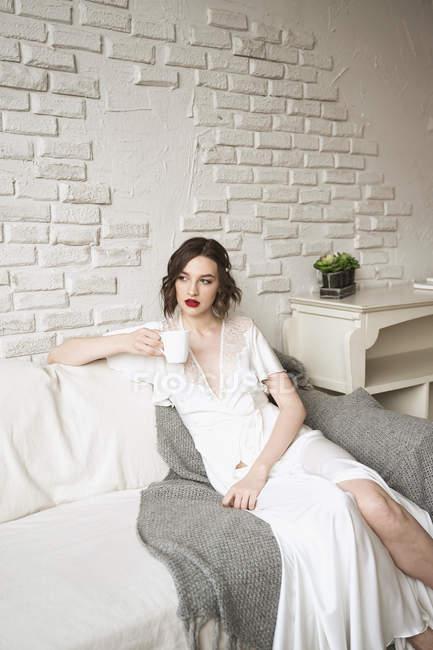 Atractiva mujer relajada reflexiva en bata de seda blanca mirando hacia otro lado y ponderando mientras está sentado en un sofá blanco y suave - foto de stock