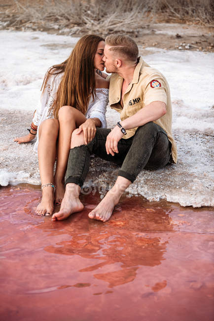 Пара цілується, сидячи на дивовижному пляжі з рожевою водою і синім небом, тримаючись за руки. — стокове фото
