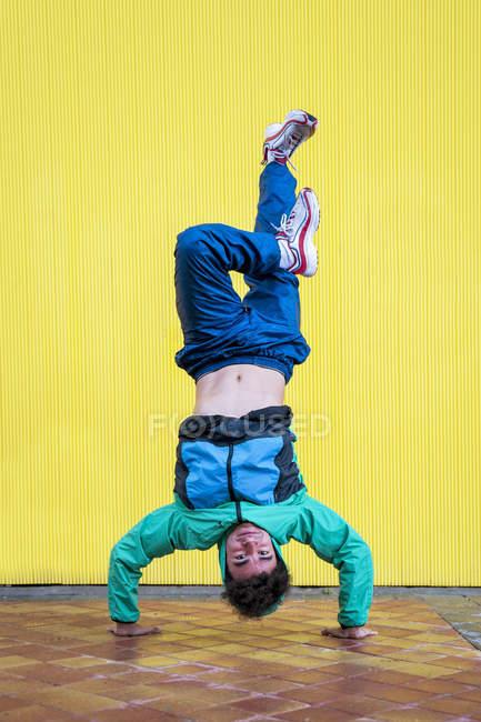 Coole lockige männliche Tänzerin in Sportbekleidung und Turnschuhen macht Handstand mit Schneidersitz gegen gelbe Wand auf der Straße — Stockfoto