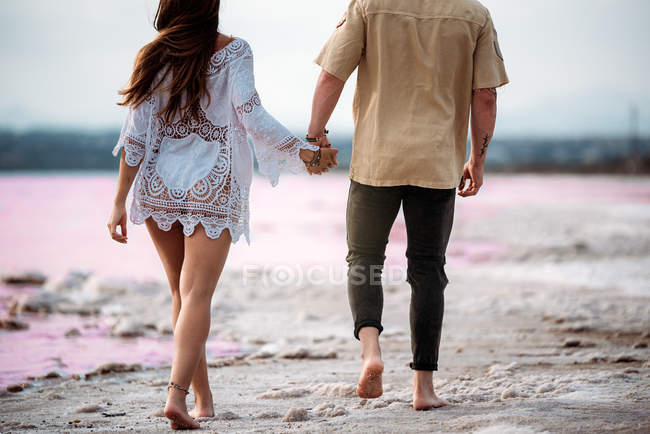 Back view of couple walking on an amazing pink lake of sea water and blue sky holding hands — Stock Photo