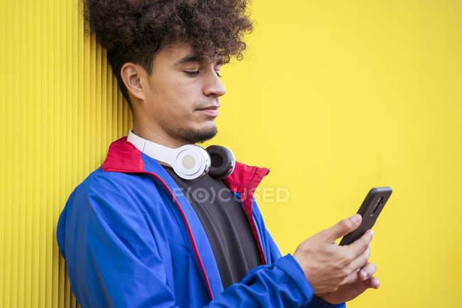 Jeune homme à capuche bleu élégant tenant le téléphone portable sur fond jaune — Photo de stock
