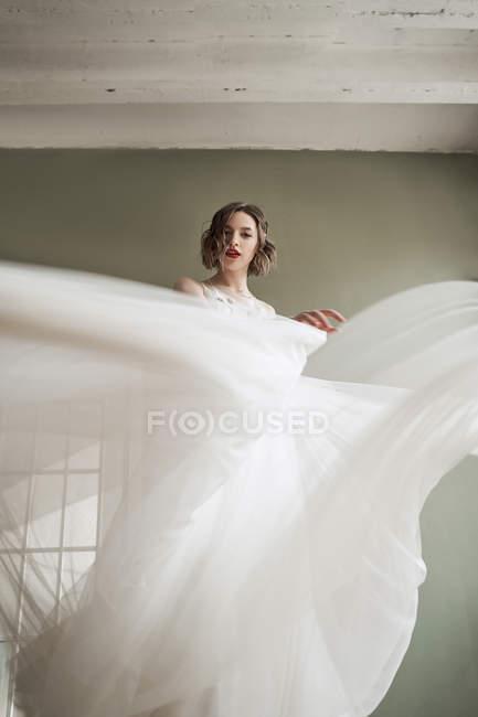 Снизу великолепная расслабленная женщина танцует и машет светлой прозрачной тканью белого свадебного платья во время подготовки к событию в квартире — стоковое фото