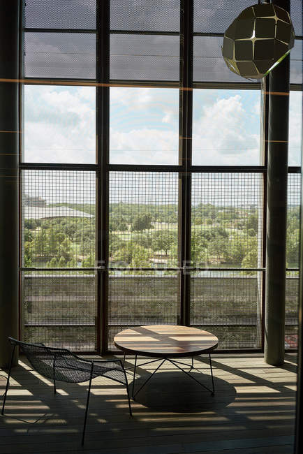 Lounge area with round wooden table and metal chair against tall windows with grid in contrast light in library Texas — Stock Photo