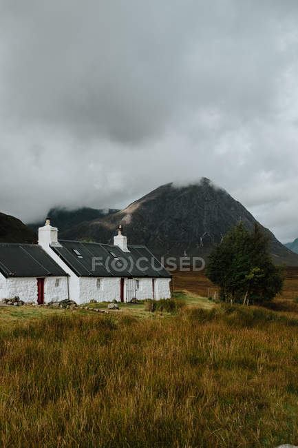 Lonely white farmhouse in autumn field in valley in Scotland surrounded by rocky hills — Foto stock