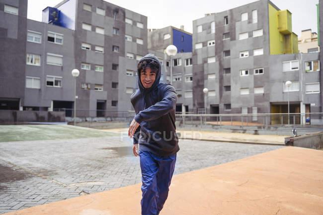 Uomo in felpa con cappuccio guardando la fotocamera tra gli edifici della città sullo sfondo durante la giornata fredda — Foto stock