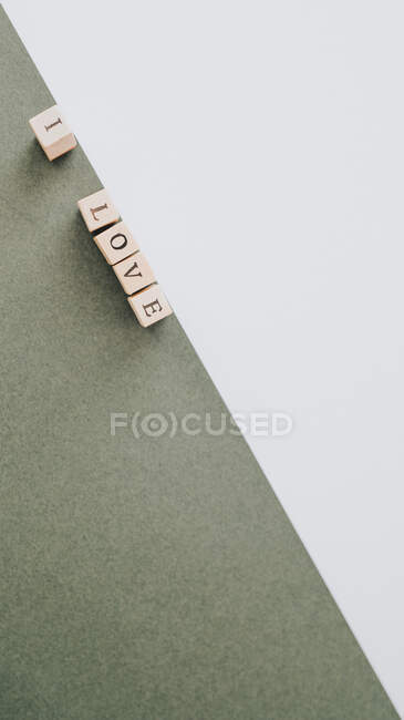 From above minimalist inscription I love made by wooden letters arranged in diagonal on green and white surface — Stock Photo