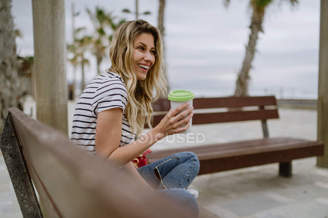 Side view of woman with takeaway cup of coffee sitting on city bench at seafront on summer day — Stock Photo