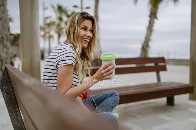 Вид сбоку женщины с чашкой кофе, сидящей на городской скамейке у моря в летний день — стоковое фото