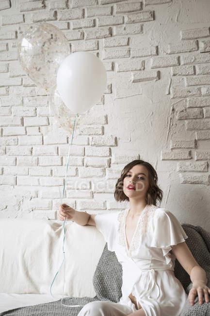 Affascinante giovane donna con labbra rosse in abito bianco sorridente alla macchina fotografica — Foto stock