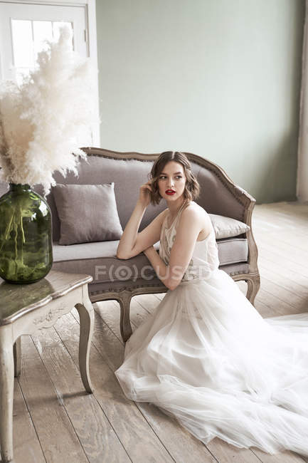 Gorgeous woman with red lips in white dress looking away while sitting on floor beside sofa — Stock Photo
