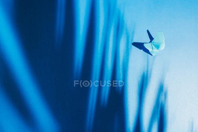 Fragiler blauer Schmetterling aus Papier mit Palmblattschatten, der an blauem Seidenstoff befestigt ist — Stockfoto