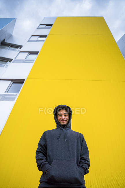 From below of male hipster in casual hoodie standing and smiling with modern yellow creative building on background — Stock Photo