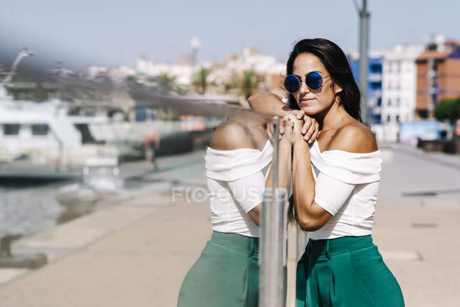 Side view of dreamy young woman with sunglasses leaning on fence and looking away on harbor dock — Stock Photo