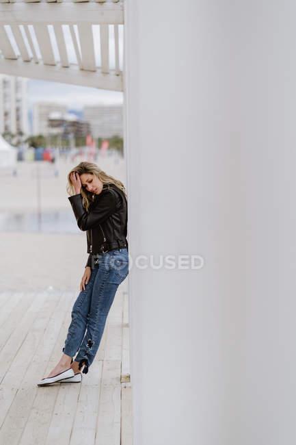 Сторона зору жінка в чорній шкіряній куртці впевнено закриті очі і спираючись на білий стовп в хмарний день — стокове фото