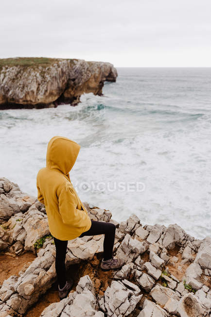 Back view of traveler in yellow warm hoodie standing alone on rocky shore looking at foamy waves on cloudy day — Stock Photo
