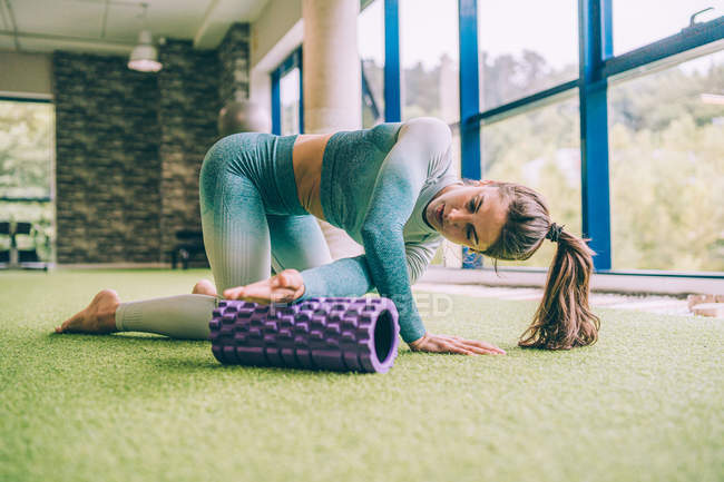 Focused fit woman in sportswear doing arm exercise with violet foam roller during workout in modern gym — Stock Photo