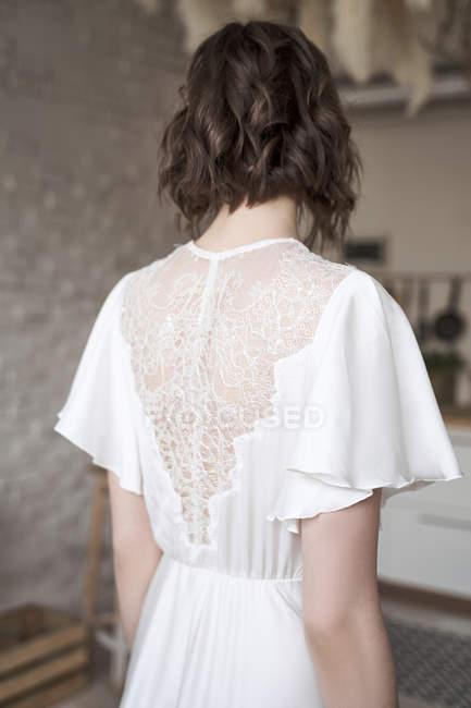 Vista posteriore della donna con in elegante bianco in piedi sulla stanza — Foto stock