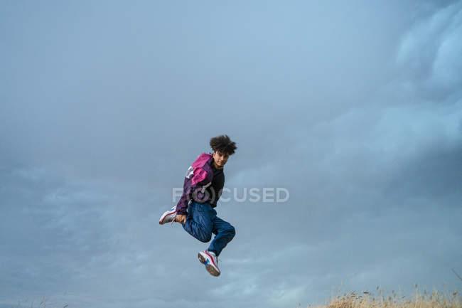 Tänzer in stylischer Aktivkleidung springen beim Breakdance mit blauem Himmel vor dem Hintergrund — Stockfoto