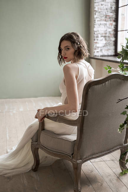 Gorgeous woman with red lips in white dress sitting on armchair — Stock Photo