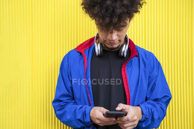 Jovem em elegante capuz azul segurando telefone celular no fundo amarelo — Fotografia de Stock
