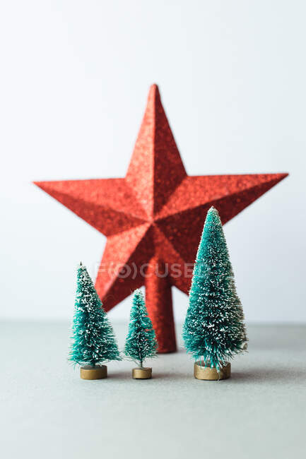 Small artificial Christmas trees on wooden stand — Stock Photo
