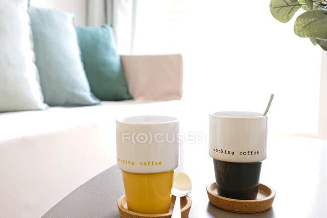 Canecas de cerâmica com café fresco colocado na mesa perto do sofá na acolhedora sala de estar em casa — Fotografia de Stock