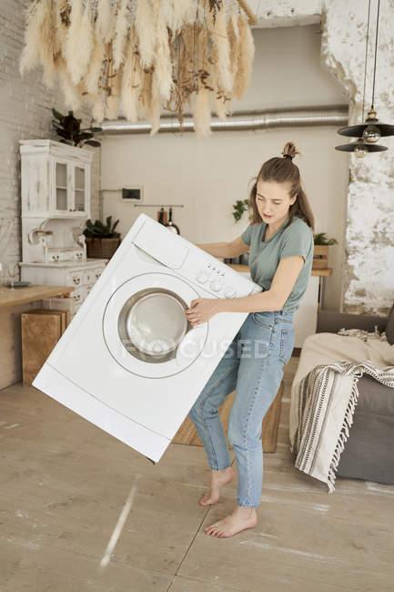 Puissante jeune femme joyeuse essayant de porter la machine à laver blanche seule dans la cuisine légère — Photo de stock