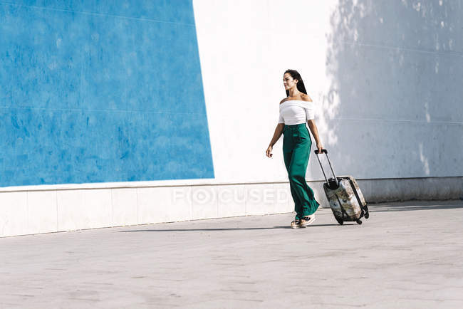Side view of young female tourist carrying a baggage while walking in street — Stock Photo