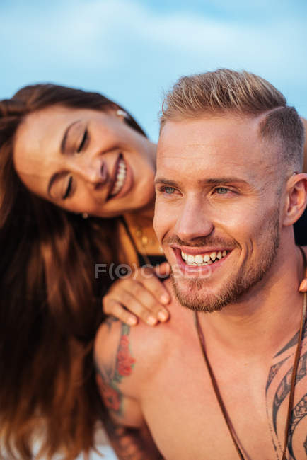 Smiling woman sitting on back of undressed tattooed boyfriend looking away with sky on background at Spain — Stock Photo