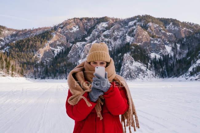 Donna che fotografa montagne innevate con smartphone — Foto stock