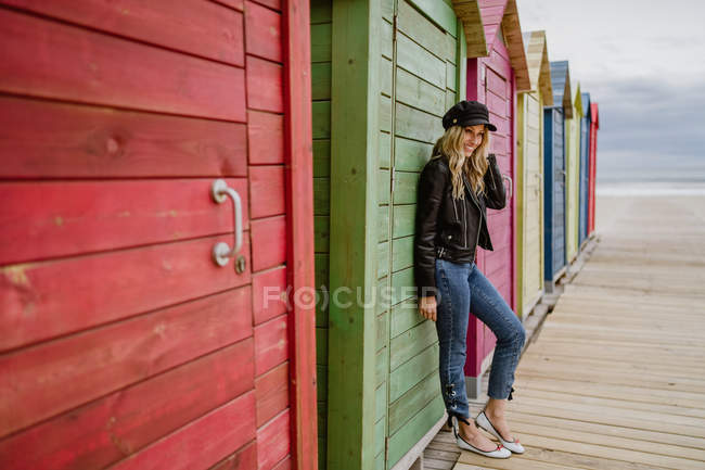 Trendy woman in black cap and leather jacket smiling brightly at camera and leaning on wall of wooden beach cabin — Stock Photo