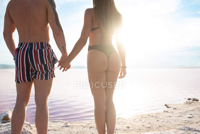 Back view of couple in swimwear standing and holding hands at beach of pink lake at Torrevieja at Spain on sunny day — Stock Photo