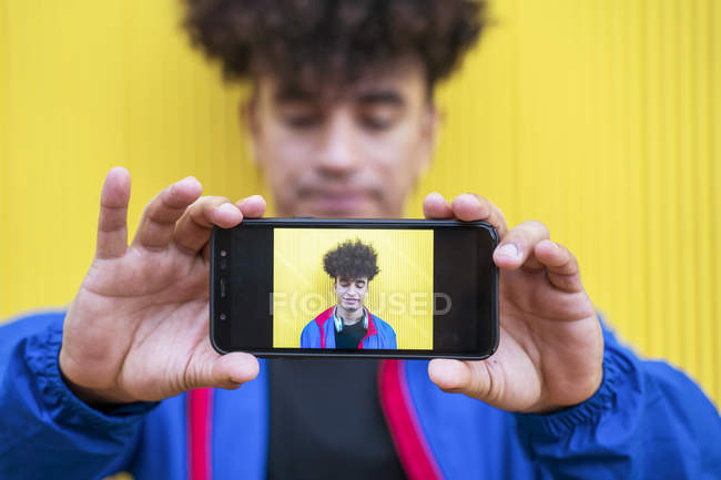 Man in stylish blue hoodie holding mobile phone with own photo in front of camera on yellow background — Stock Photo