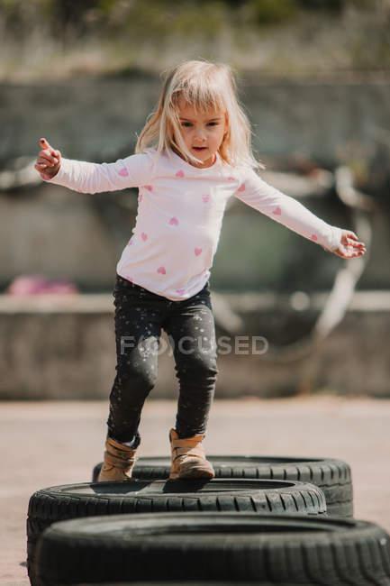 Feliz menina alegre se divertindo e andando através da linha de pneus de carro preto enquanto joga ao ar livre no dia de verão — Fotografia de Stock